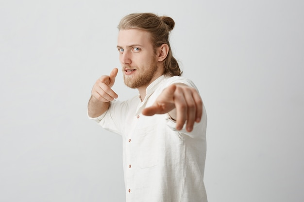 Уверенный мачо со светлыми волосами и булочкой, указывая на камеру указательными пальцами,