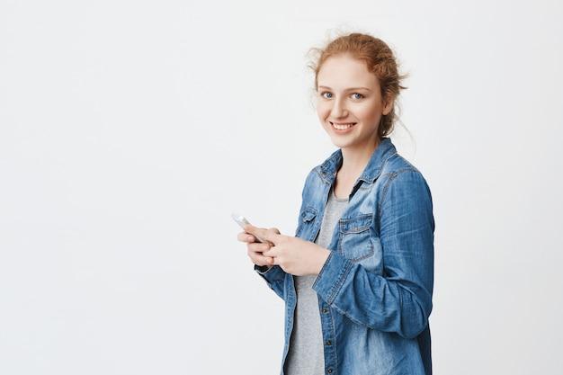 Снимок эмоциональной молодой рыжеволосой девушки с милой улыбкой, стоящей наполовину повернутой с причесанными волосами, держащей смартфон, глядя на камеру, в джинсовой рубашке