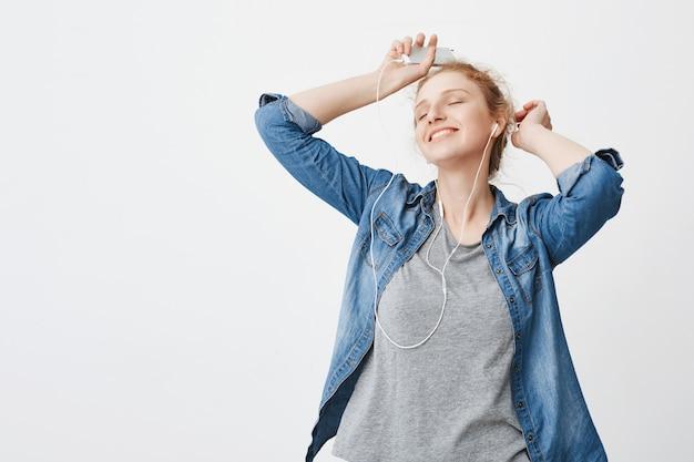 興奮した幸せな白人赤毛の女の子が上げられた手でヘッドフォンで音楽を聴きながら踊り、スマートフォンを持ち、灰色の空間でのんきな