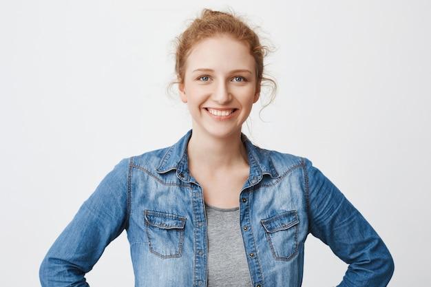 Талия-вверх портрет милой счастливой европейской рыжей модели с волосами, расчесанными в булочке, держащей руки на талии