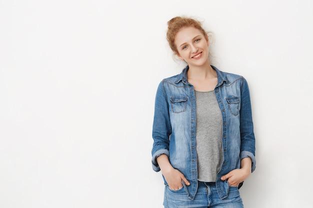 Красивая рыжая кавказская с голубыми глазами, опираясь на серое пространство, держа руки в джинсах