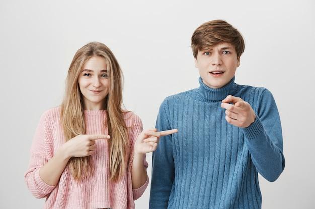 Взволнованная молодая пара в вязаных свитерах активно жестикулирует