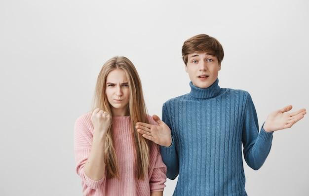 怒っているブロンドの女の子が拳を振ると脅して、男は肩をすくめて混乱