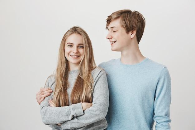 ボーイフレンドはガールフレンドを抱擁し、彼女に微笑んでいます。