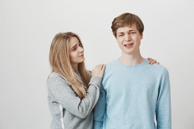 Девушка показывает сострадание. сестра утешает брата, который чувствует себя подавленным