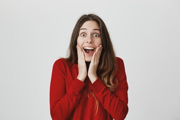 Удивленная счастливая женщина слышит хорошие новости, удивленно улыбаясь и задыхаясь