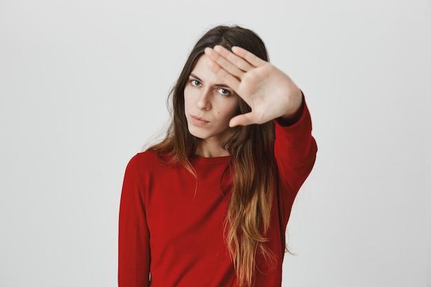 Раздраженная, разозленная женщина протягивает руку, останавливая движение, не желая быть застреленным