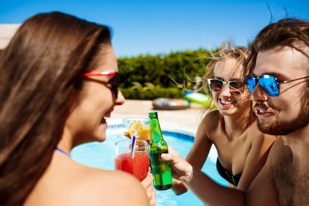 Друзья говорят, улыбаются, пьют коктейли, отдыхают, отдыхают возле бассейна