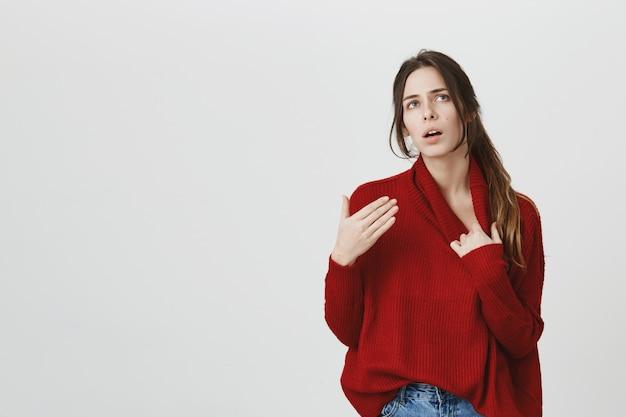セーターの若い魅力的な女性は暑く感じます