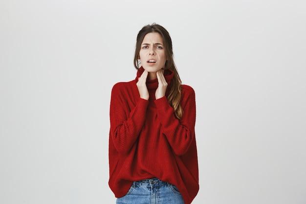 首に触れる病気の女性、炎症、喉の痛み