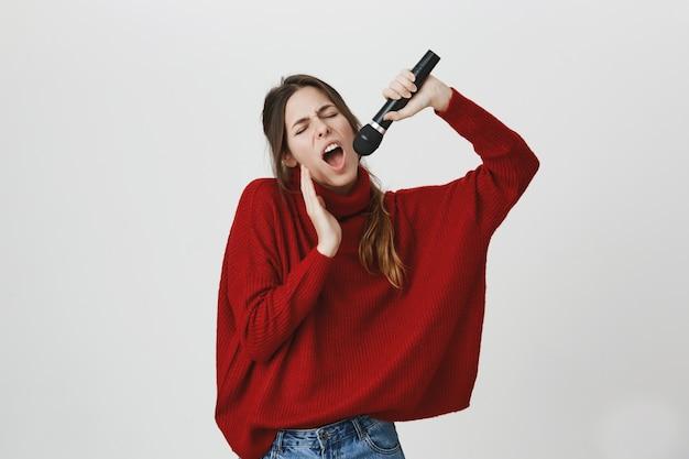 幸せな魅力的な女性がカラオケを歌って、マイクを握る