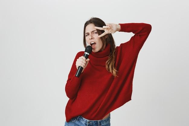 生意気なかわいい女性がカラオケで歌って、ピースサインを表示