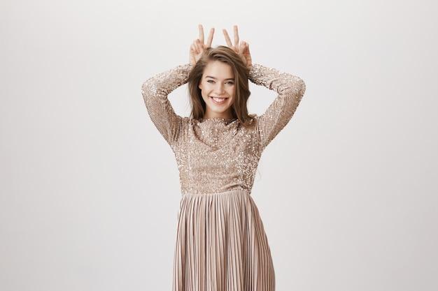 Улыбающаяся шикарная женщина показывает знаки мира, надевает вечернее платье