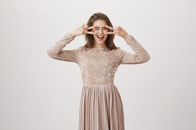 Нахальная гламурная женщина в вечернем платье, показывает знак мира