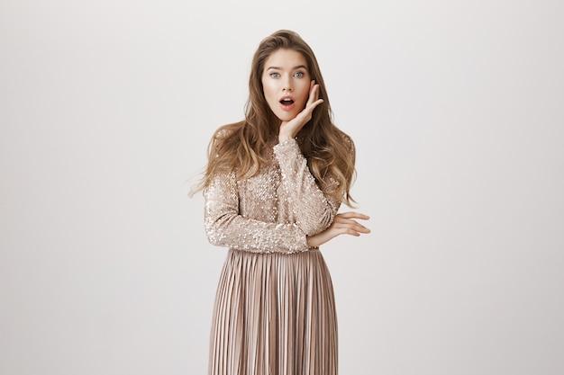 驚いた女性の口を開けて、魅力のイブニングドレスを着てください。