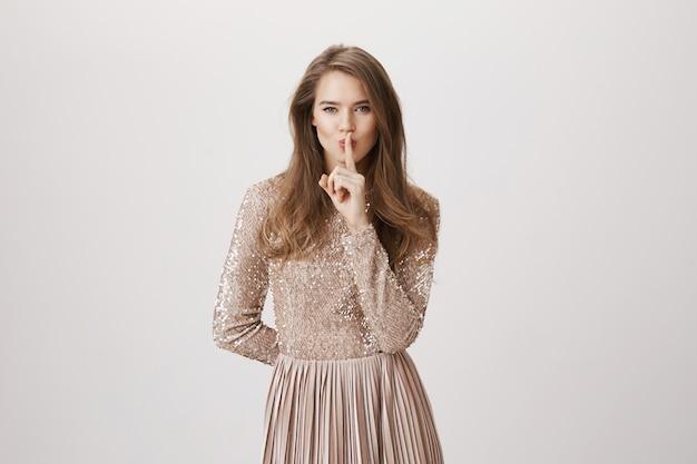 官能的な女性のイブニングドレスの静けさ、唇に指を押す