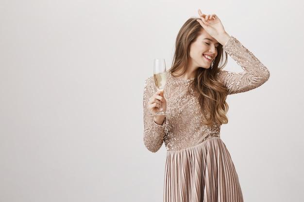 Счастливая танцующая женщина в вечернем платье держит бокал с шампанским