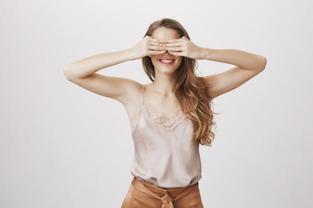 Улыбающаяся привлекательная женщина закрывает глаза ладонями