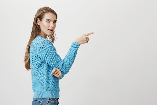 Под впечатлением женщина повернуть на камеру и указывая пальцем вправо