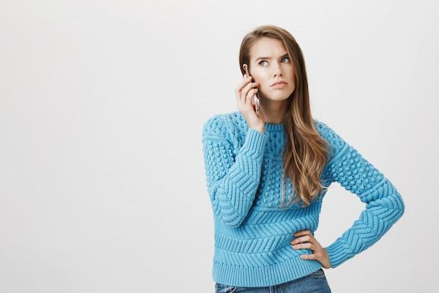 電話に掛かっている腹が立つ女性