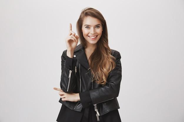 スマートな魅力的な女性が提案をし、人差し指を上げる