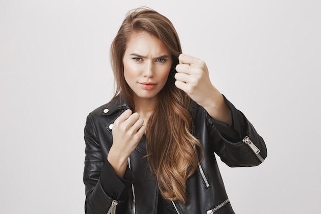 Крутая и дерзкая женщина сжимает кулаки, стоит в позе боксера