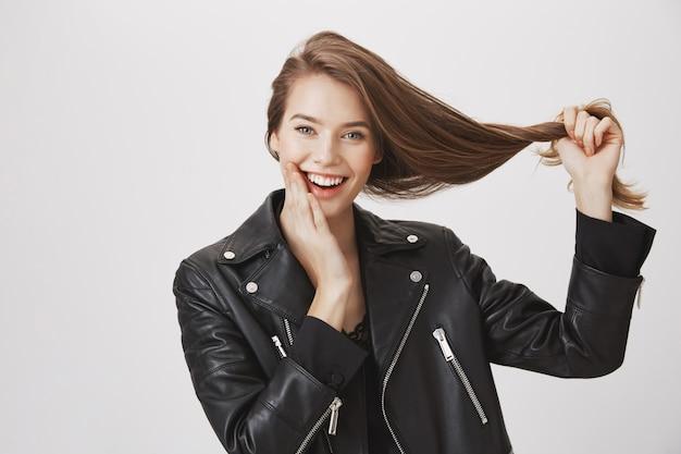 Усмехаясь молодая женщина вытягивает волосы, концепцию продуктов ухода за волосами