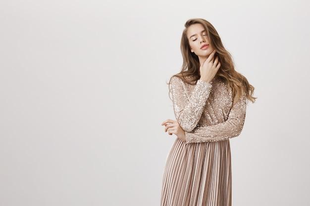 官能的なゴージャスな女性のイブニングドレスで目を閉じて肌に触れる