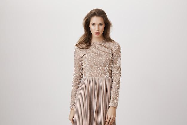 スタイリッシュなイブニングドレスの豪華な生意気な女