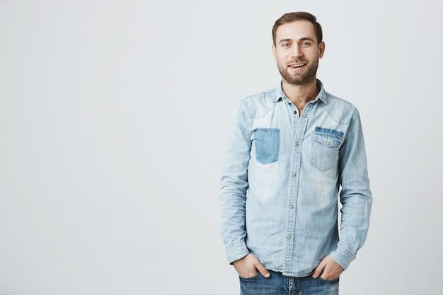 デニムシャツでハンサムな若いひげを生やした男はポケットに手をつなぐ