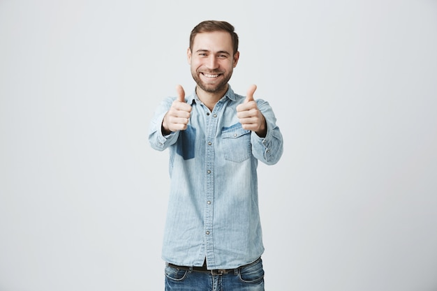 親指のジェスチャーを示すひげの幸せな興奮した男