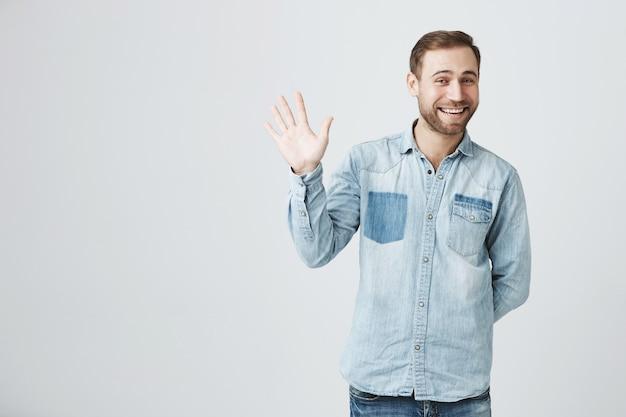Скромный милый бородатый мужчина говорит привет, машет рукой в приветствии