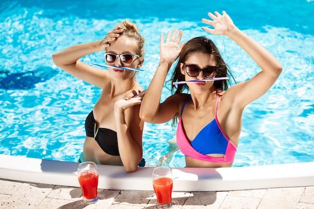 Молодые красивые девушки улыбаются, обманывают, говорят, отдыхают в бассейне.