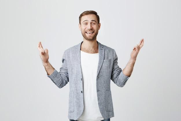 Счастливый обнадеживающий человек скрестил пальцы, загадывая желание