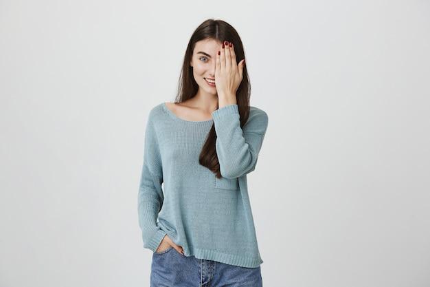 Улыбающаяся привлекательная женщина покрывает половину лица ладонью