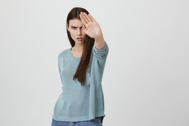 怒っている深刻な女性が一時停止の標識を表示、禁止または不承認