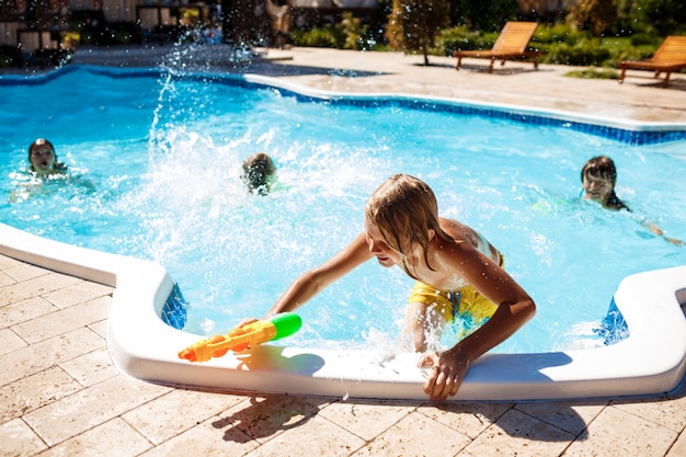 陽気な子供たちは水鉄砲を遊んで、喜び、ジャンプ、プールで泳いでいます。