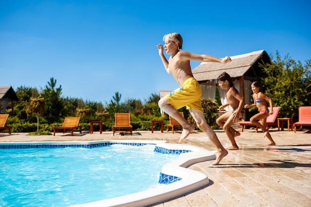 陽気な子供たちは、喜び、ジャンプ、プールで泳いでいます。