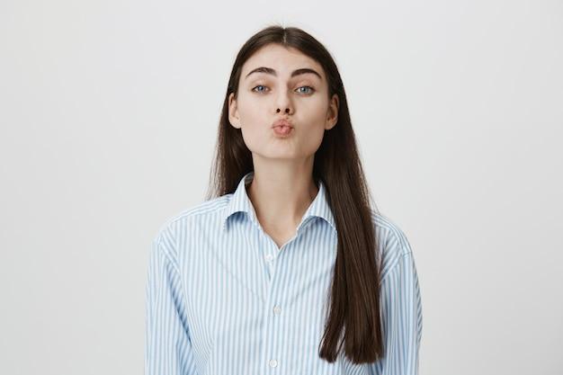 Милая романтическая женщина складывает губы для поцелуя