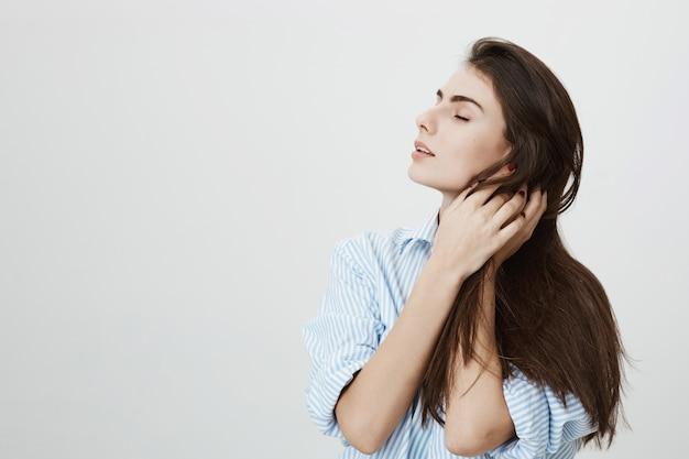 官能的な情熱的な女性の髪に触れる、夢のような目を閉じて