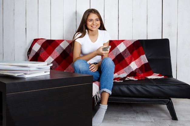 テレビを見て、笑みを浮かべて、自宅のソファーに座っていた美しい女性。