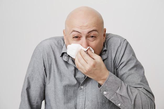 Больной лысый парень средних лет чихает в салфетку