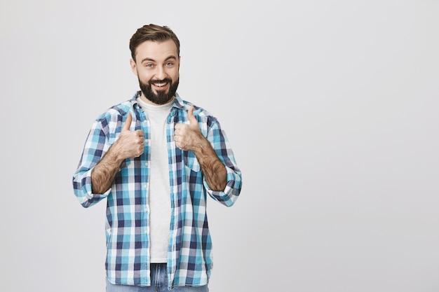 陽気な満足しているひげを生やした男は親指を立てて笑顔