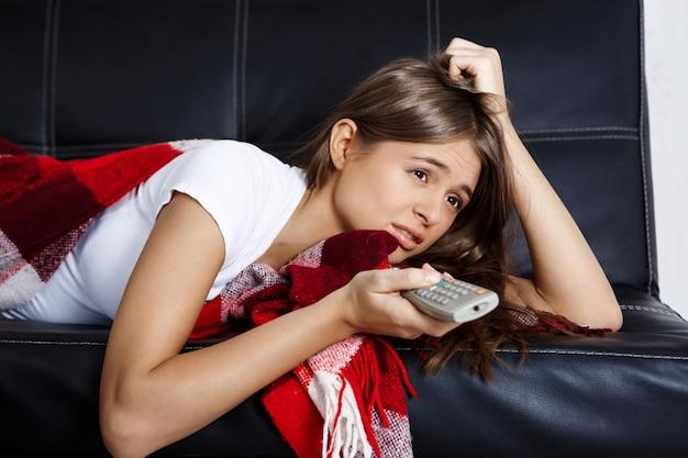 テレビを見て、自宅のソファーに横になっている退屈美しい女性。