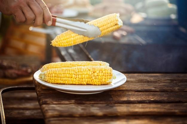 Молодой человек жарения кукурузы на гриле.