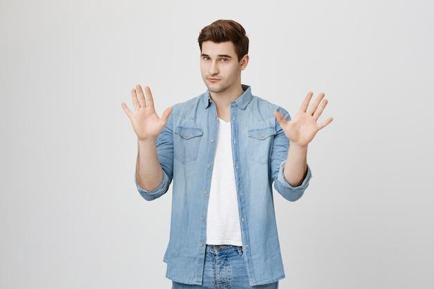 Серьезный красивый мужчина показывает жест стоп, поднимает руки вверх, не согласен