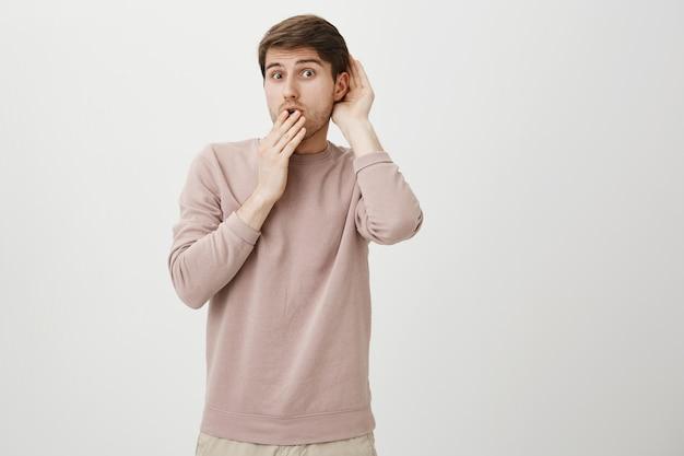 Заинтригованный милый парень подслушивает, держа руку возле уха