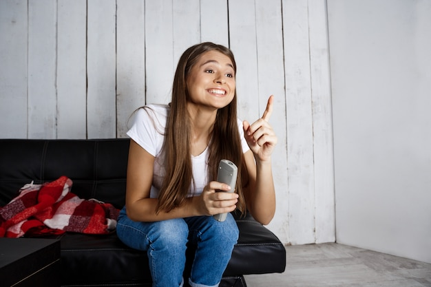 テレビを見て、自宅のソファーに座っている陽気なきれいな女性。