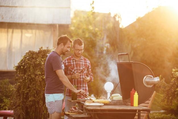 Молодые человеки жаря барбекю на гриле в сельской местности коттеджа.