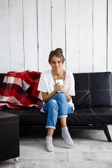 笑みを浮かべて、カップを保持している、ソファーに座っていた若い美しい女性。